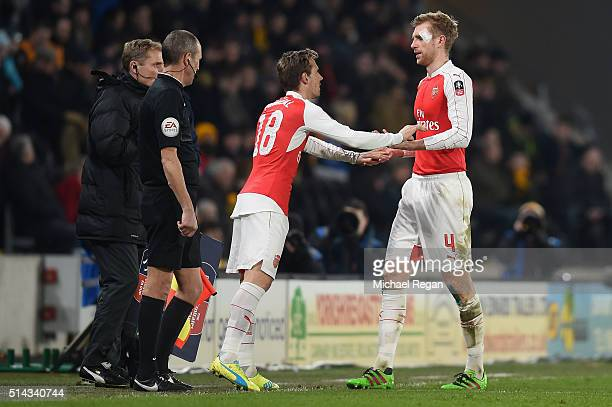 Per Mertesacker of Arsenal is replaced by Nacho Monreal of Arsenal after his head injury during the Emirates FA Cup Fifth Round Replay match between...