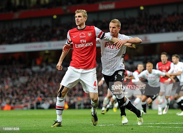 Per Mertesacker of Arsenal is shadowed by Brede Hangeland of Fulham during the Barclays Premier League match between Arsenal and Fulham at Emirates...