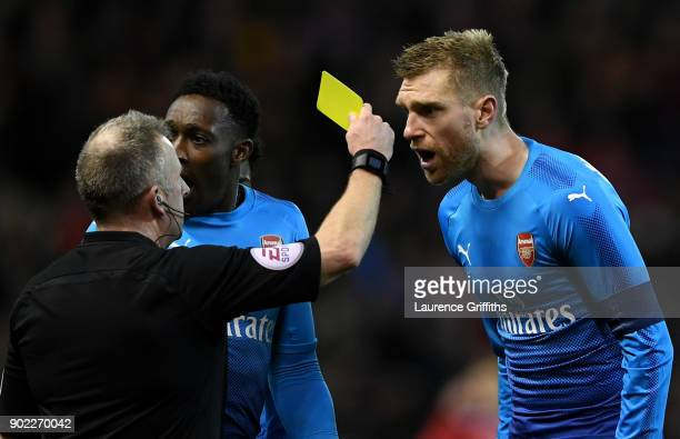 Per Mertesacker of Arsenal is shown the yellow card by referee Jonathan Moss after he awarded Nottingham Forest's fourth goal during The Emirates FA...