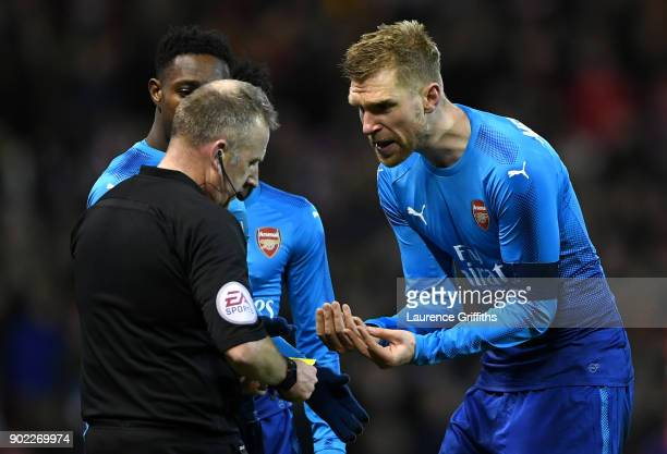 Per Mertesacker of Arsenal reacts with referee Jonathan Moss after he awarded Nottingham Forest's fourth goal during The Emirates FA Cup Third Round...
