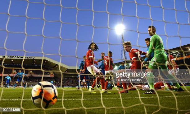 Per Mertesacker of Arsenal scores his team's first goal during The Emirates FA Cup Third Round match between Nottingham Forest and Arsenal at City...