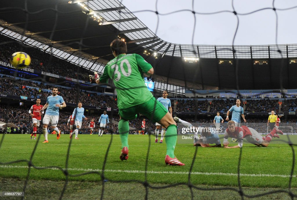Per Mertesacker of Arsenal (R) scores his team's third goal past goalkeeper Costel Pantilimon of Manchester City during the Barclays Premier League match between Manchester City and Arsenal at Etihad Stadium on December 14, 2013 in Manchester, England.