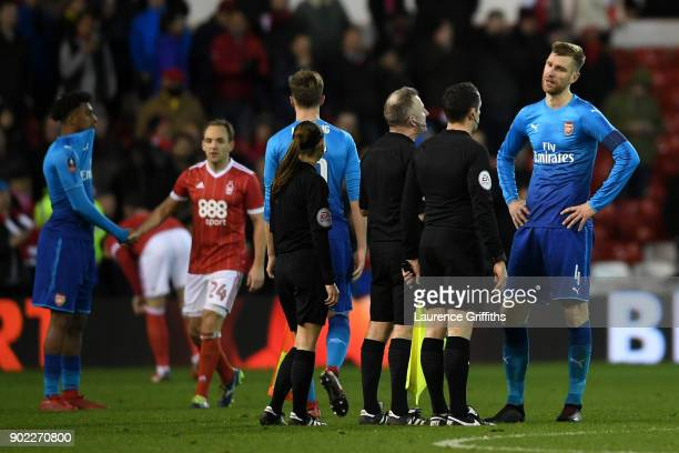 Per Mertesacker of Arsenalargues with referee Jonathan Moss after The Emirates FA Cup Third Round match between Nottingham Forest and Arsenal at City...