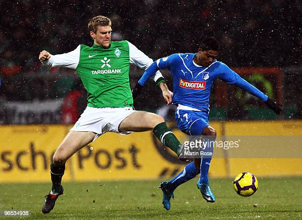 Per Mertesacker of Bremen and Maicousel of Hoffenheim battle for the ball during the DFB Cup quarter final match between SV Werder Bremen and 1899...