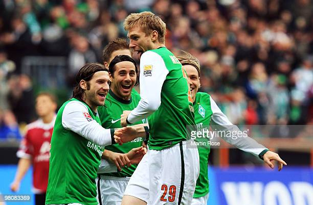 Per Mertesacker of Bremen celebrate with his team mates after scoring his team's opening goal during the Bundesliga match between Werder Bremen and...