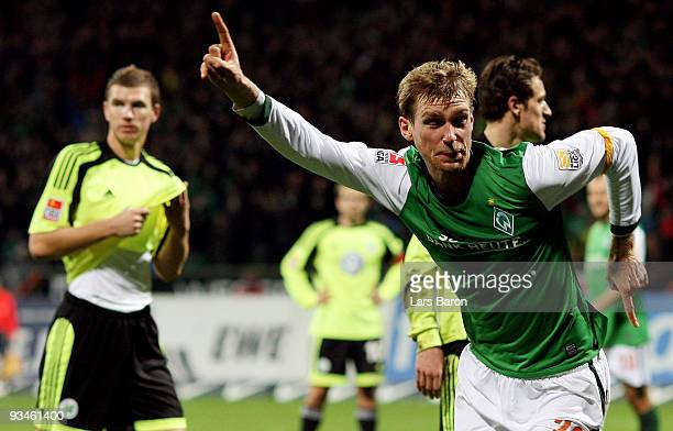 Per Mertesacker of Bremen celebrates after scoring his teams second goal next to Edin Dzeko of Wolfsburg, who scored two goals for his team, during...