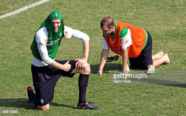 Per Mertesacker of Bremen protects his head against the heat during the Werder Bremen training session at the Al Wasl training ground on January 7...