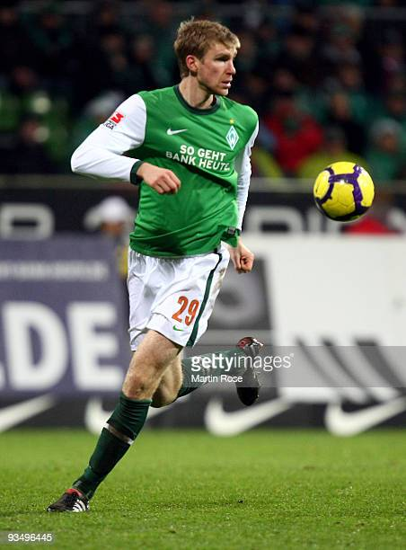 Per Mertesacker of Bremen runs with the ball during the Bundesliga match between Werder Bremen and VfL Wolfsburg at the Weser stadium on November 28...