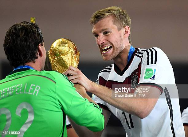 Per Mertesacker of Germany holds the World Cup trophy to celebrate with his teammates during the award ceremony after the 2014 FIFA World Cup Brazil...