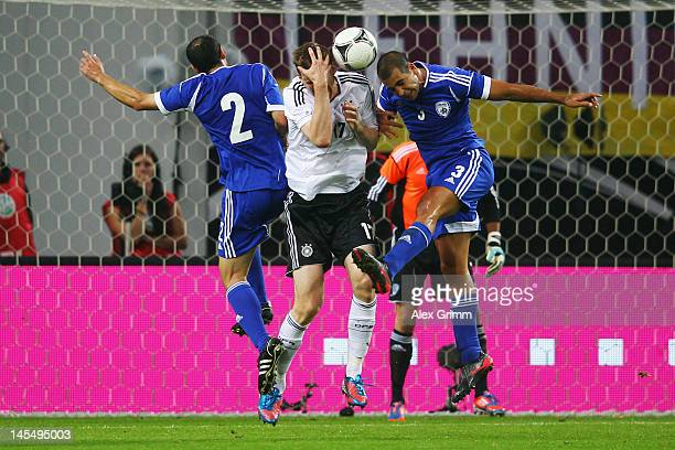 Per Mertesacker of Germany jumps for a header with Yuval Shpungin and Tal Ben Haim of Israel during the international friendly match between Germany...