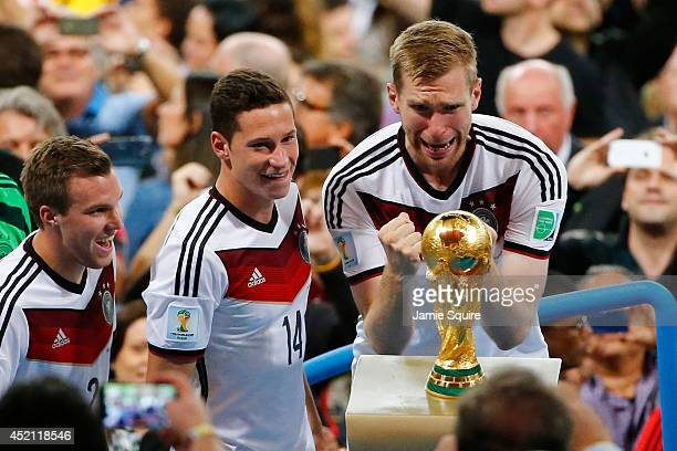 Per Mertesacker of Germany reacts towards the World Cup trophy after defeating Argentina 10 in extra time during the 2014 FIFA World Cup Brazil Final...