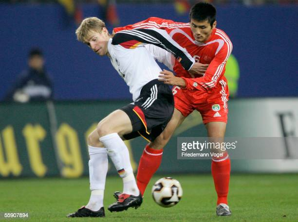 Per Mertesacker of Germany tussles for the ball with Jia yi Shao of China during the friendly game between Germany and China at the AOL Arena on...