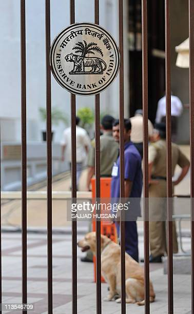 Security personnel stand near the Reserve Bank of India logo in Mumbai on May 3 2011 India's central bank raised lending rates by a...