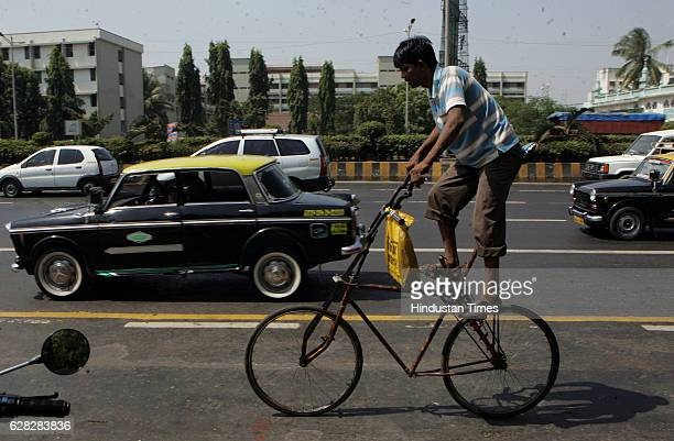 Perched high on his bicycle seat this young man seems to be on a trip of his own pedaling along the busy Western Express highway at Kalanagar in...
