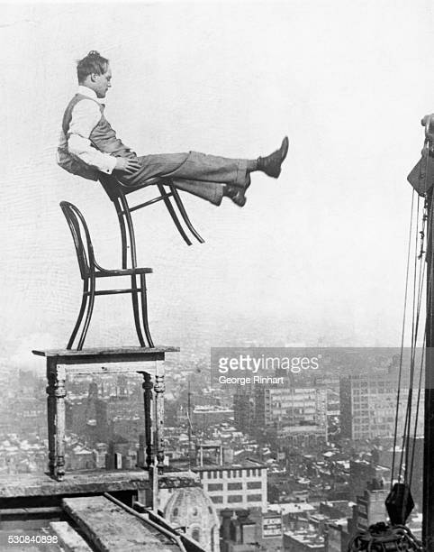 Perched on a girder at the edge of a building under construction a confident daredevil balances on the back legs of a chair atop another chair set on...