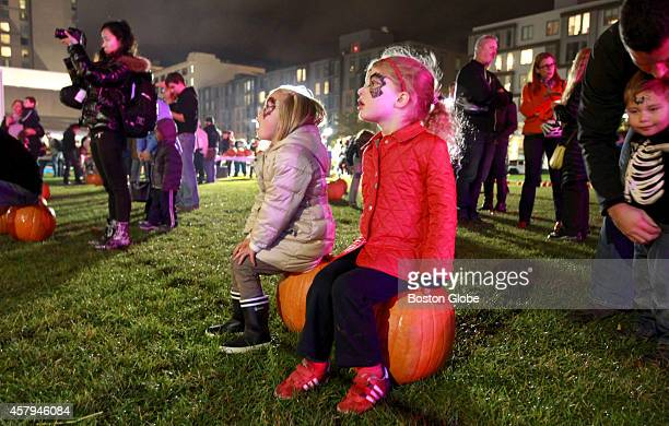 Perched on pumpkins Marion Smith left and Cassandra Moeder take in the show during Punkin' Fest at the Lawn on D Street in South Boston Mass October...