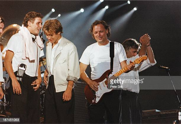 Percussionist Gary Wallis and bass guitarist Guy Pratt with David Gilmour and Richard Wright of Pink Floyd at the end of their performance on stage...