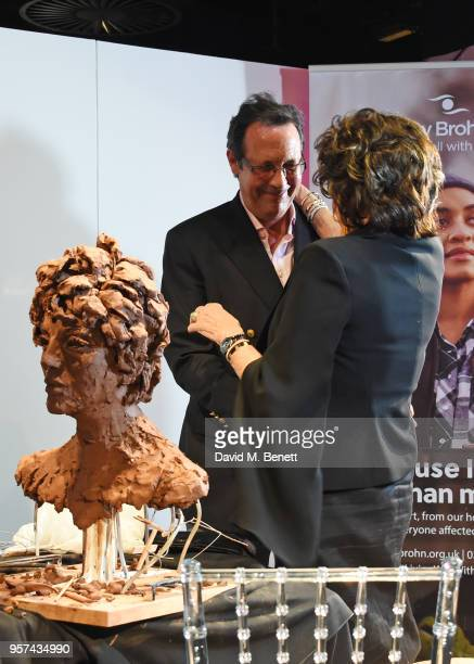 Percy Gibson and Dame Joan Collins poses at a live sculpting in support of Penny Brohn UK Charity at the London Film Museum on May 11 2018 in London...
