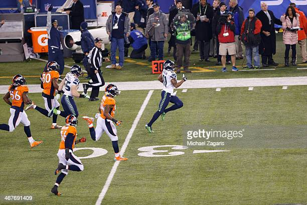 Percy Harvin of the Seattle Seahawks returns the opening kickoff of the second half for a 87yard touchdown during Super Bowl XLVIII against the...
