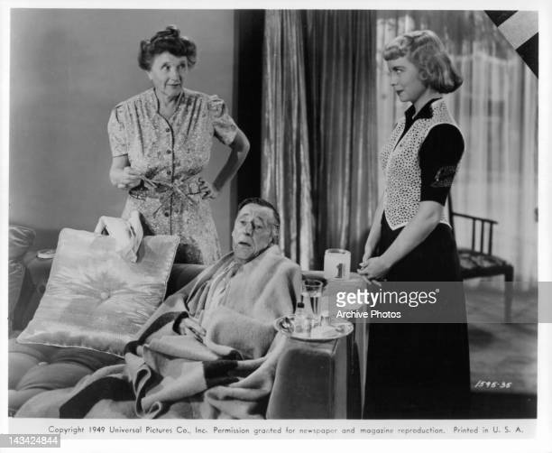 Percy Kilbride wrapped in blanket with Marjorie Main and Meg Randall standing beside him in a scene from the film 'Ma and Pa Kettle' 1949