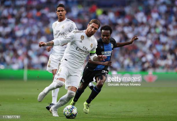 Percy Tau of Club Brugge battles for possession with Sergio Ramos of Real Madrid during the UEFA Champions League group A match between Real Madrid...