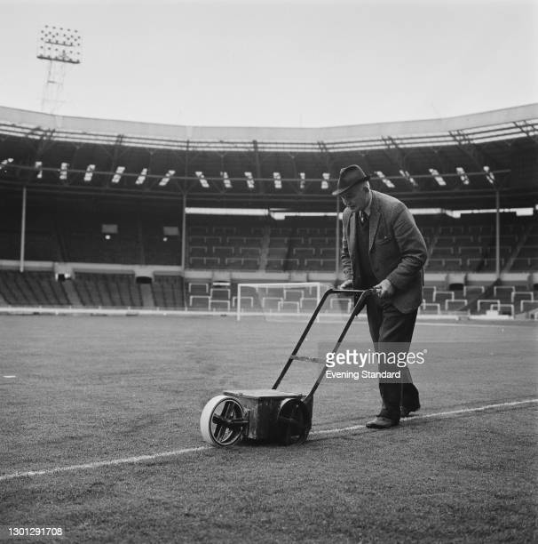 Percy Young, head groundsman at Wembley Stadium in London, using a line marker to prepare the pitch for the 1973 FA Cup Final, UK, 5th May 1973.