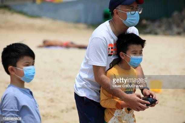 Pere et son fils portant un masque de protection contre le Covid-19 sur la plage de Stanley le 26 Avril 2020. Hong Kong Chine.