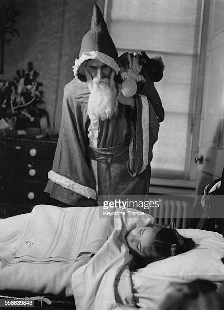 Pere Noel regardant une petite fille endormie dans le dortoir de l'orphelinat Reed's School de Dogmersfield Park a Basingstoke RoyaumeUni le 22...