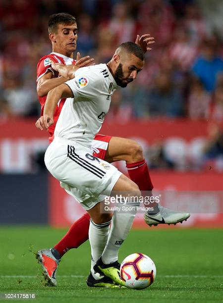 Pere Pons of Girona competes for the ball with Karim Benzema of Real Madrid during the La Liga match between Girona FC and Real Madrid CF at...