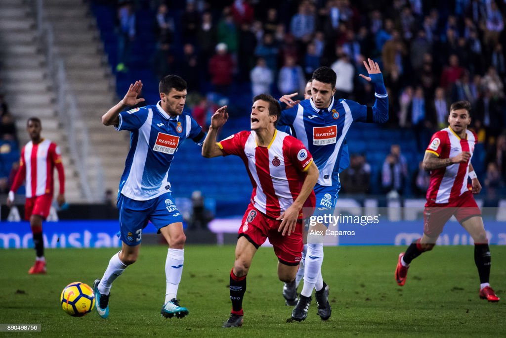Pere Pons of Girona FC advances with the ball between Aaron Martin (L) and Mario Hermoso (R) of RCD Espanyol during the La Liga match between RCD Espanyol and Girona FC at RCDE Stadium on December 11, 2017 in Barcelona, Spain.