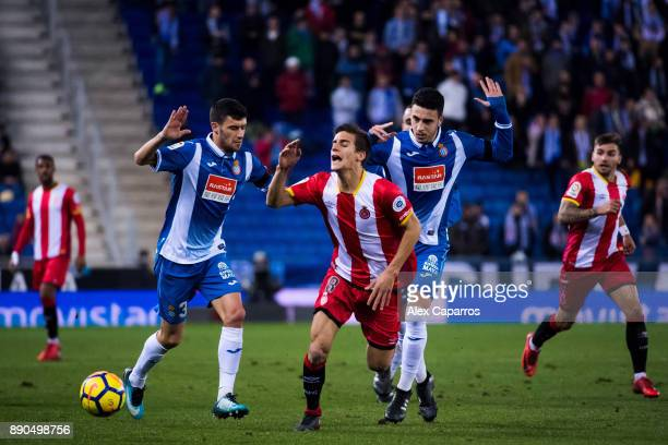 Pere Pons of Girona FC advances with the ball between Aaron Martin and Mario Hermoso of RCD Espanyol during the La Liga match between RCD Espanyol...