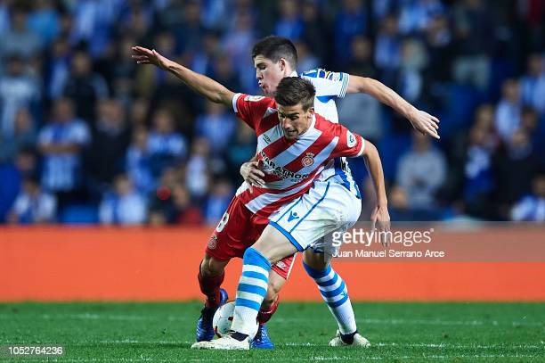 Pere Pons of Girona FC competes for the ball with Aritz Elustondo of Real Sociedad during the La Liga match between Real Sociedad and Girona FC at...