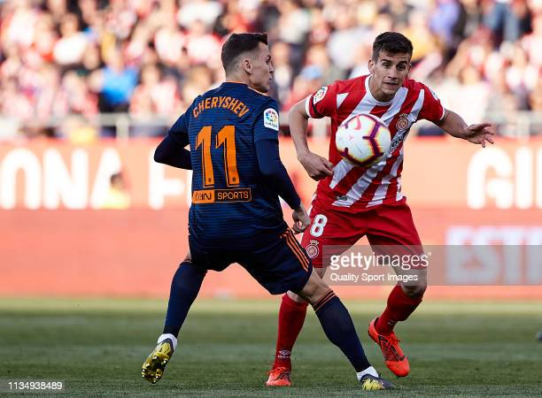 Pere Pons of Girona FC competes for the ball with Denis Cheryshev of Valencia CF during the La Liga match between Girona FC and Valencia CF at...