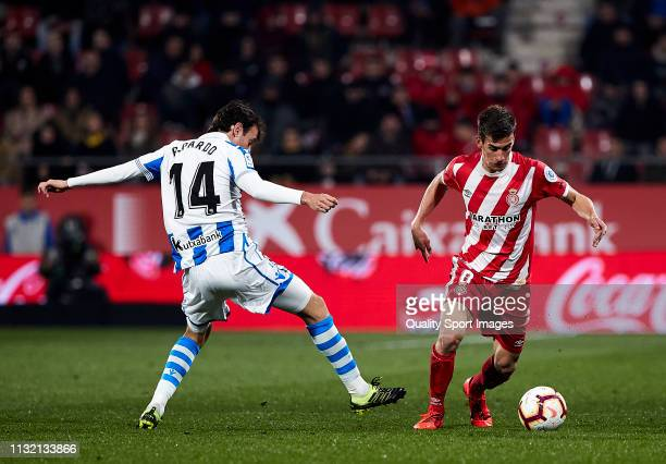 Pere Pons of Girona FC competes for the ball with Ruben Pardo of Real Sociedad during the La Liga match between Girona FC and Real Sociedad at...