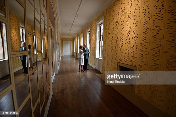 Peregrine Cavendish, Duke of Devonshire and Amanda, Duchess of Devonshire pose for a photograph between panels of ceramic blocks which represent...