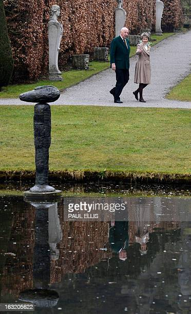Peregrine Cavendish Duke of Devonshire and his wife Amanda Duchess of Devonshire walk past a sculpure entitled 'Sun Gazer' by British artist William...