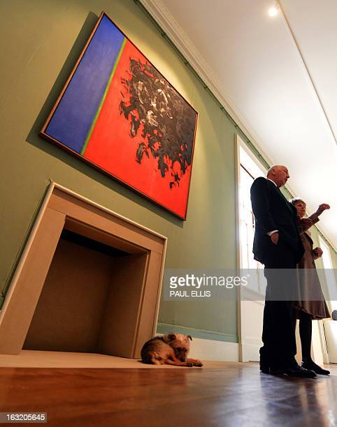 Peregrine Cavendish Duke of Devonshire and his wife Amanda Duchess of Devonshire stand in front of a painting entitled '151958' by British artist...