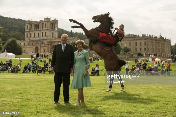 Peregrine 'Stoker' Cavendish, Duke of Devonshire, and his wife Amanda, Duchess of Devonshire pose with members of the Ukranian Cossack Stunt Team as...