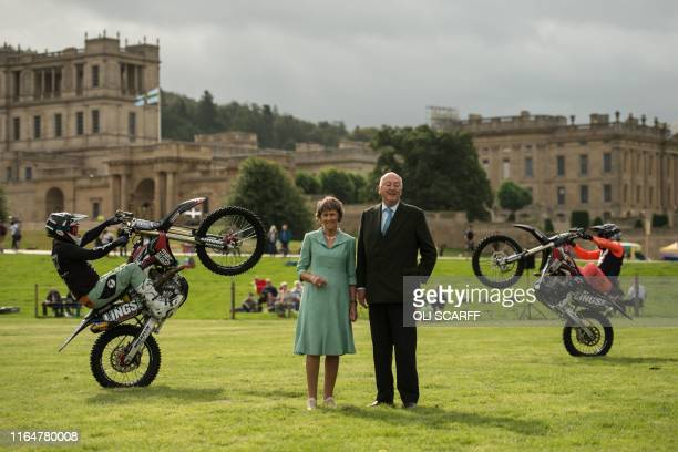Peregrine 'Stoker' Cavendish, Duke of Devonshire, and his wife Amanda, Duchess of Devonshire pose with members of the Bolddog Lings FMX Display Team...