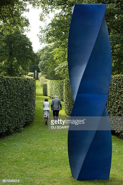 Peregrine 'Stoker' Cavendish Duke of Devonshire and his wife Amanda Duchess of Devonshire walks away from a sculpture by artist Alexander...