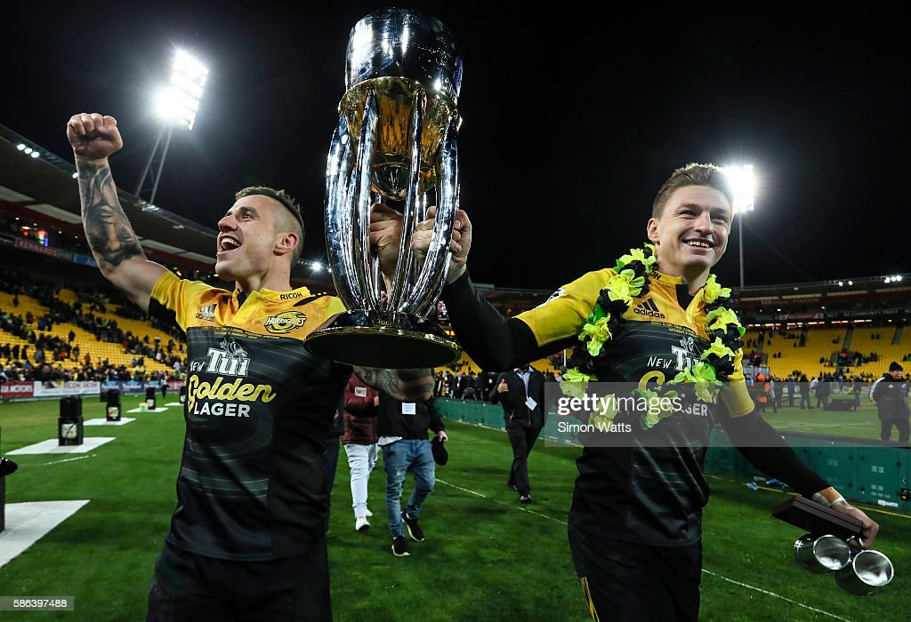 TJ Perenara (L) and Beauden Barrett of the Hurricanes celebrate with the Super Rugby Trophy after the Hurricanes won the 2016 Super Rugby Final match between the Hurricanes and the Lions at Westpac Stadium on August 6, 2016 in Wellington, New Zealand.