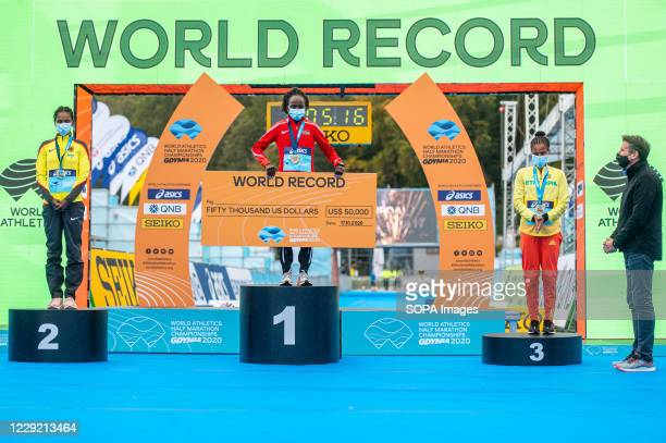 Peres Jepchirchir of Kenya with a cheque for beating the world record silver Melat Yisak Kejeta of Germany and bronze Yalemzerf Yehualaw of Ethiopia...