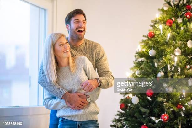 young heterosexual couple standing christmas tree