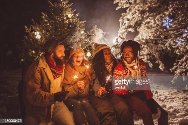 perfect christmas tree arrival celebrated with sparklers - public celebratory event stock pictures, royalty-free photos & images