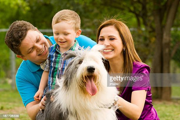 Perfect Family Playing with Dog Outdoors.