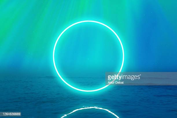 perfect green neon ring glowing over the sea with stunning northern lights in iceland. - spirituality stock pictures, royalty-free photos & images
