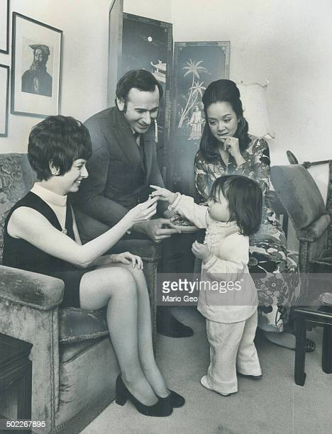 Perfect Hostess Kyra Clarkson who will be 2 next month hands a candy to guest Mrs Helen Collins while parents Stephen and Adrienne Clarkson look on...