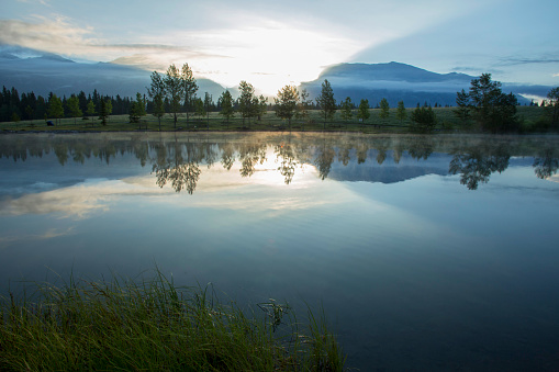 Perfect reflection of forest and mountains in lake at sunrise 1162607263