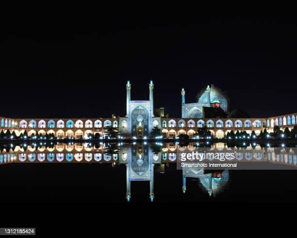 "perfect reflection of ""masjed-e shah"" mosque (""shah mosque"") illuminated at night in isfahan, iran - イマームホメイニ広場 ストックフォトと画像"