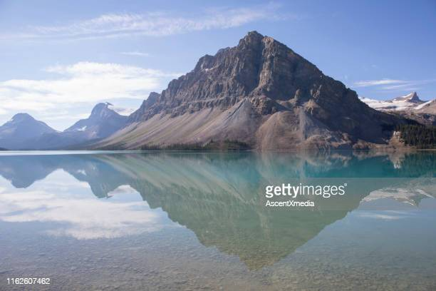 perfect reflection of mountains in a calm lake - bow river stock pictures, royalty-free photos & images